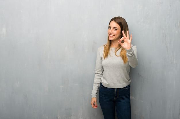 Giovane donna sulla parete strutturata che mostra un segno giusto con le dita