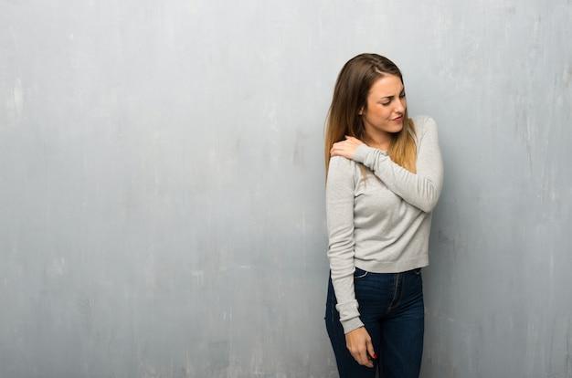 Giovane donna sulla parete strutturata che soffre dal dolore alla spalla per aver fatto uno sforzo