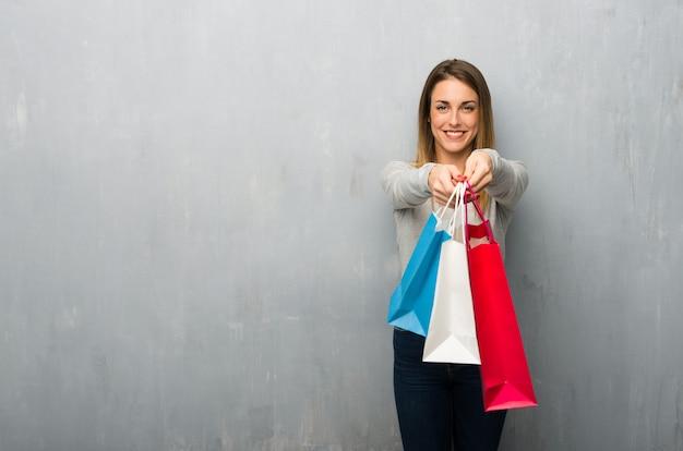 Giovane donna sulla parete strutturata che tiene molti sacchetti della spesa