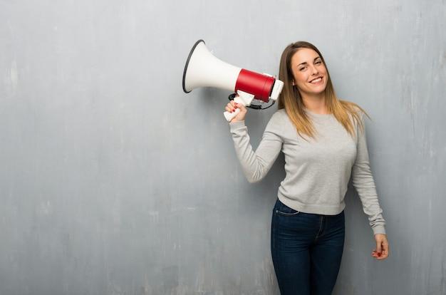 Giovane donna sulla parete strutturata che tiene un megafono