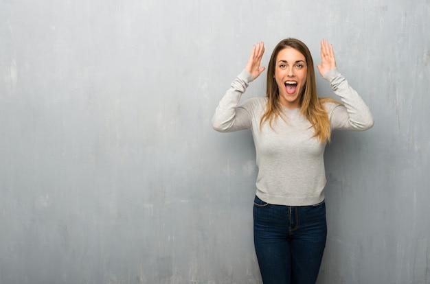 Giovane donna sulla parete strutturata con espressione facciale sorpresa e scioccata