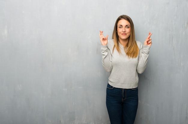 Giovane donna sulla parete strutturata con le dita che attraversano e che desiderano il meglio