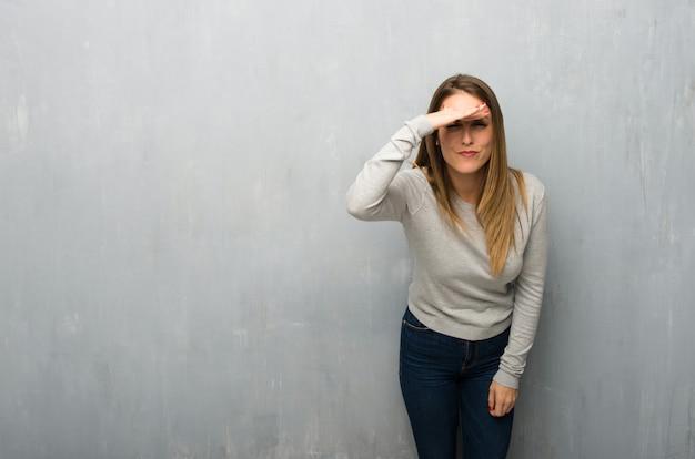 Giovane donna sulla parete strutturata guardando lontano con la mano per guardare qualcosa