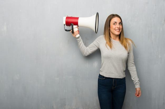Giovane donna sulla parete strutturata prendendo un megafono che fa molto rumore