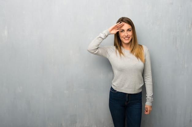 Giovane donna sulla parete strutturata salutando con la mano