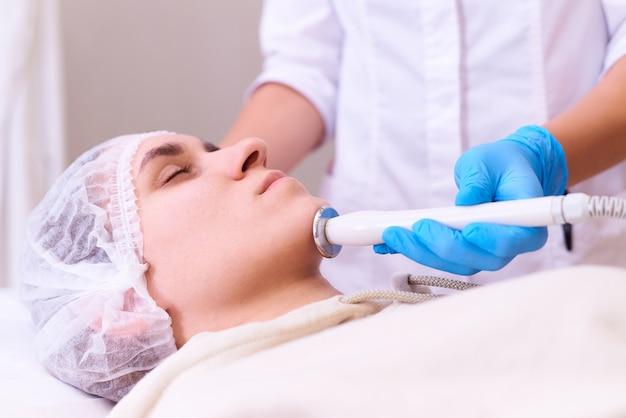 Giovane donna sulla procedura di lifting facciale rf in una clinica di cosmetologia