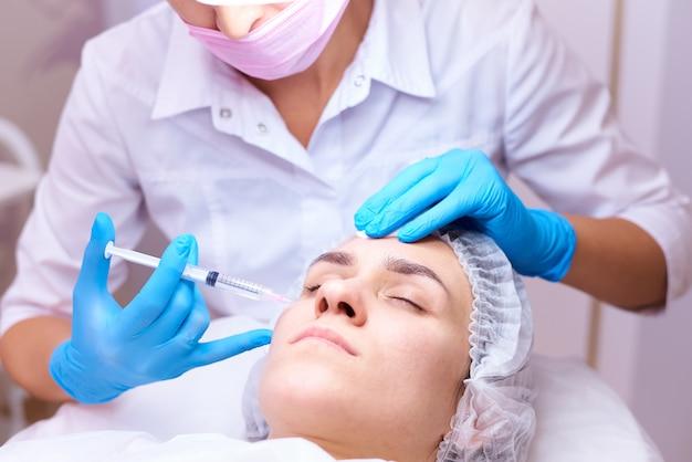 Giovane donna sulla procedura di ringiovanimento in una clinica di cosmetologia