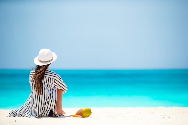 Giovane donna sulla spiaggia bianca con cocco