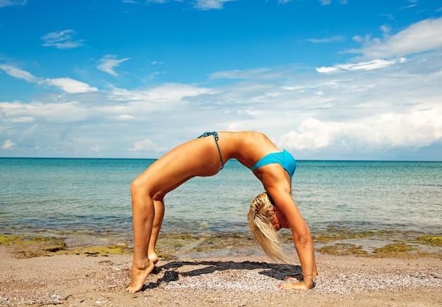 Giovane donna sulla spiaggia che fa esercizio di yoga di forma fisica. elemento acroyoga per forza ed equilibrio