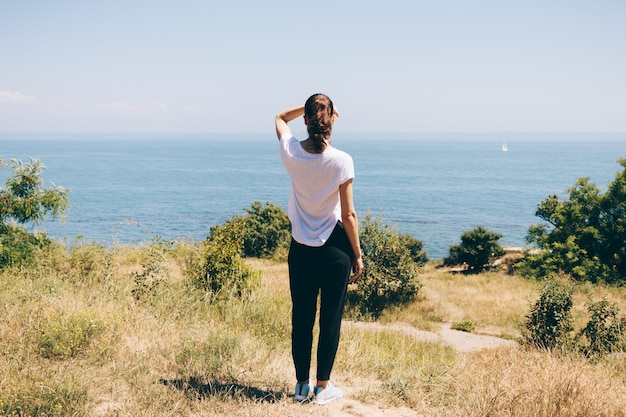 Giovane donna sulla spiaggia guardando il mare