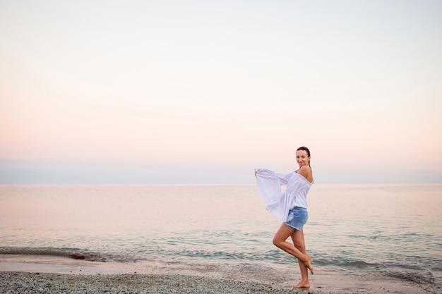 Giovane donna sulla spiaggia in vacanza europea sulla costa ligure nel tramonto