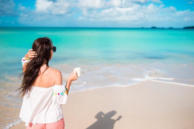Giovane donna sulla spiaggia punto di vista posteriore della ragazza con la tazza di caffè in riva al mare