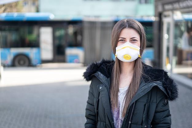 Giovane donna sulla strada con maschera contro l'inquinamento