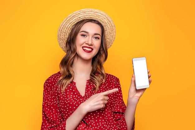 Giovane donna sveglia allegra che indica un dito su uno schermo bianco del telefono cellulare isolato su uno spazio giallo del modello della parete per progettazione
