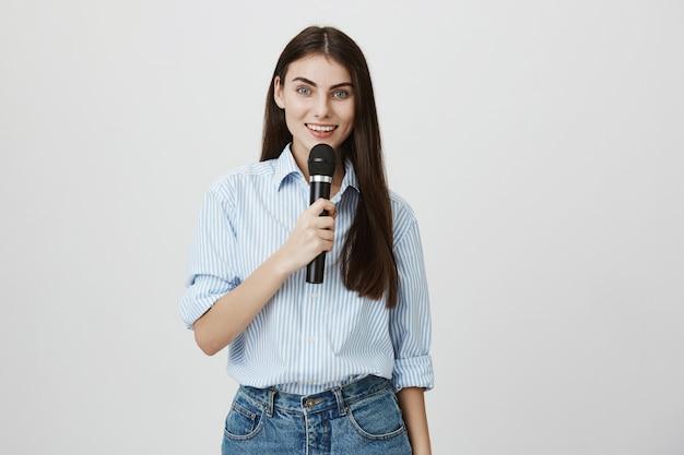 Giovane donna sveglia che fa discorso nel microfono