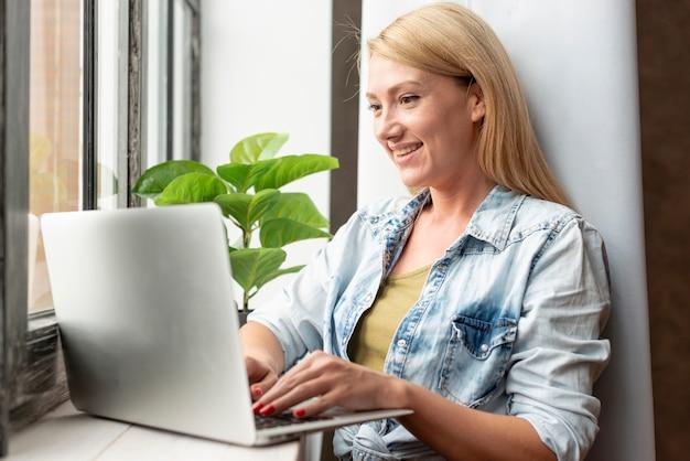 Giovane donna sveglia che lavora ad un computer portatile