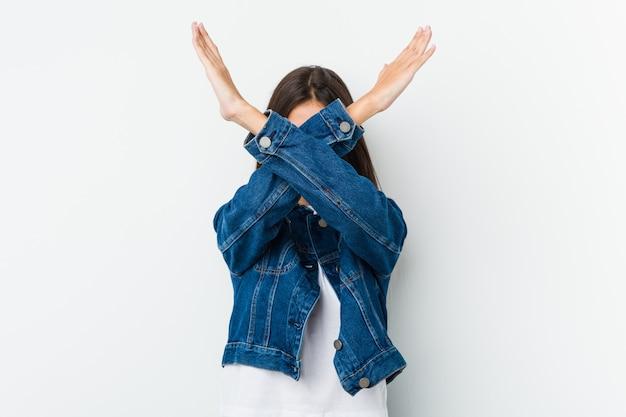 Giovane donna sveglia che mantiene due armi attraversate, concetto di rifiuto.