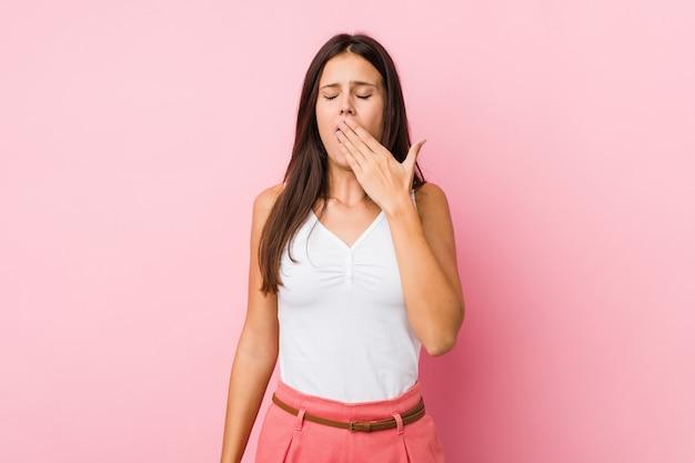 Giovane donna sveglia che sbadiglia mostrando una bocca stanca della copertura di gesto.