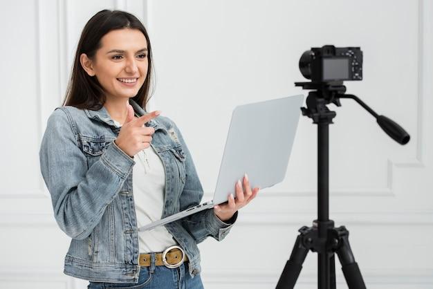 Giovane donna sveglia che sorride sulla macchina fotografica