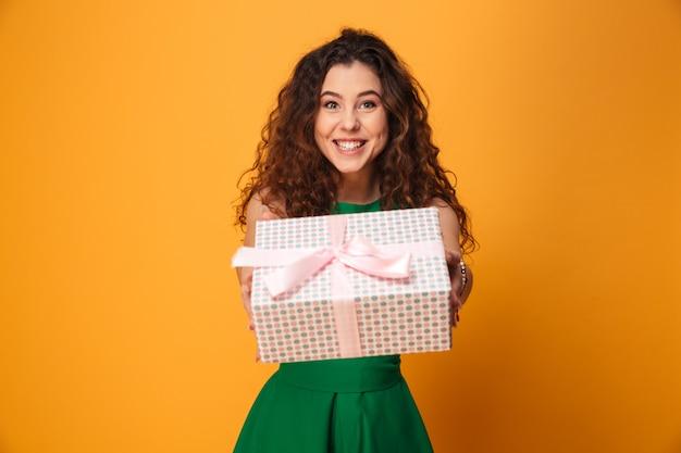 Giovane donna sveglia che tiene il contenitore di regalo attuale.