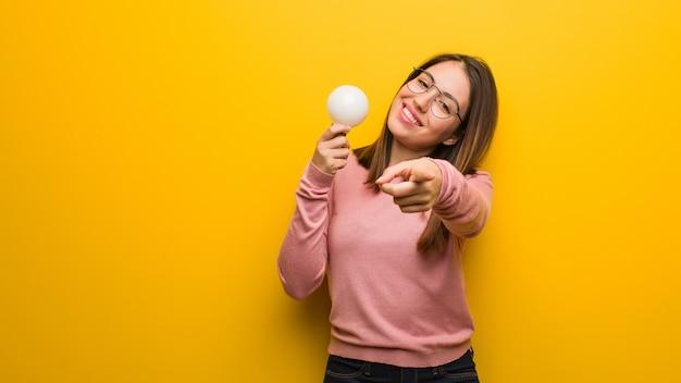 Giovane donna sveglia che tiene una lampadina allegra e sorridente che indica alla parte anteriore