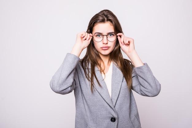 Giovane donna sveglia di affari con i vetri su fondo bianco