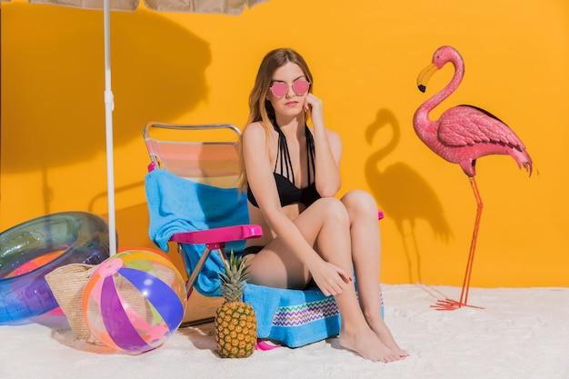 Giovane donna sveglia in costume da bagno che riposa sulle chaise longue in studio