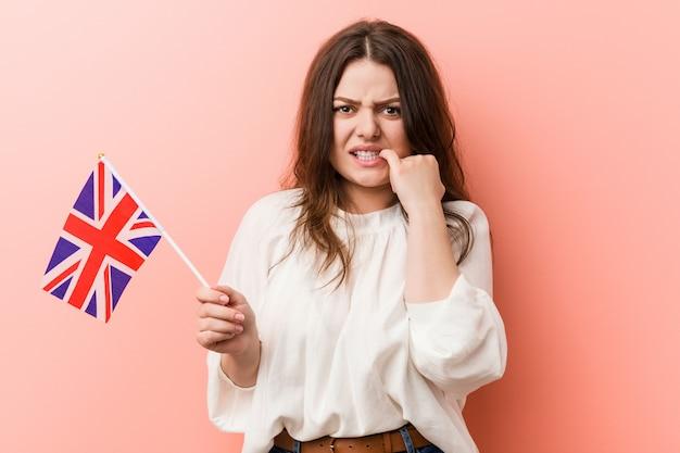 Giovane donna taglie forti con una bandiera del regno unito che morde le unghie, nervosa e molto ansiosa.