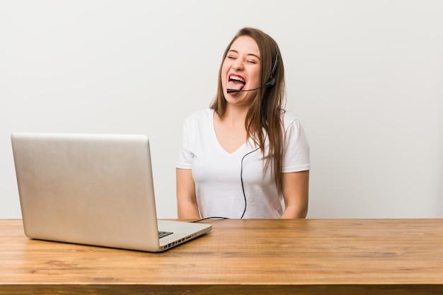 Giovane donna telemarketer divertente e amichevole che attacca fuori lingua.