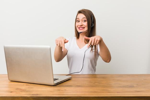 Giovane donna telemarketer punta verso il basso con le dita, sensazione positiva.