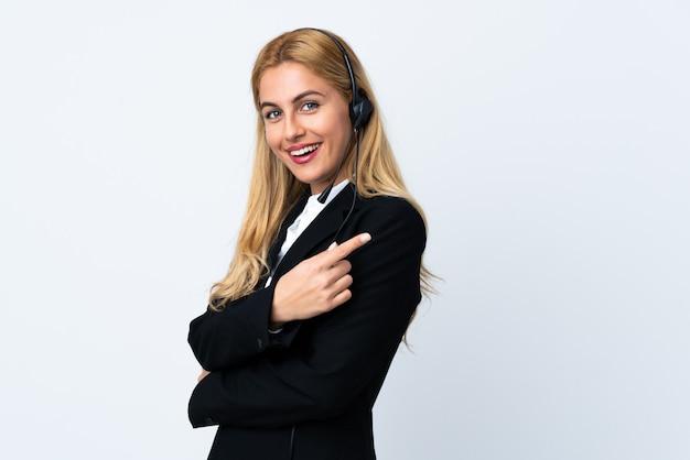 Giovane donna telemarketer sopra bianco isolato che punta al lato per presentare un prodotto