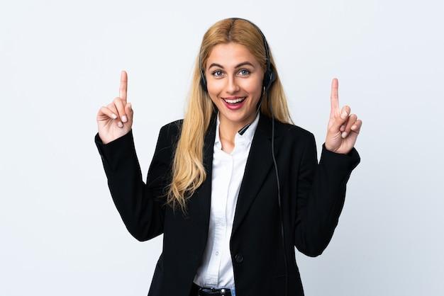 Giovane donna telemarketer sul muro bianco rivolta verso l'alto una grande idea