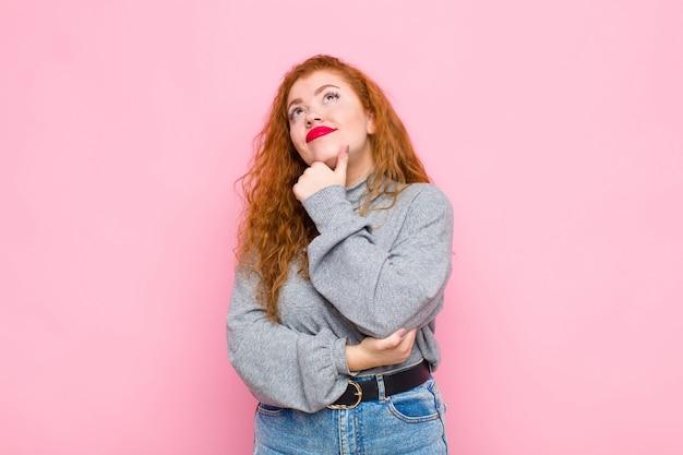 Giovane donna testa rossa sentirsi pensieroso, chiedersi o immaginare idee, sognare ad occhi aperti e cercare di copiare lo spazio sul muro rosa