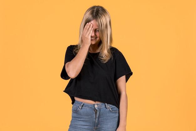 Giovane donna timida che sta contro il fondo colorato luminoso