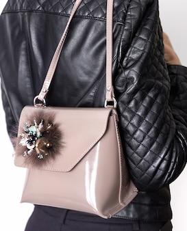 Giovane donna torna in giacca di pelle nera con borsetta verniciata rosa