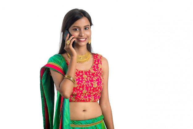 Giovane donna tradizionale indiana che per mezzo di un telefono cellulare o di uno smartphone isolato su bianco