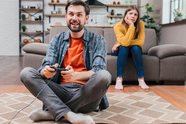 Giovane donna triste che esamina uomo che gioca il video gioco con la leva di comando