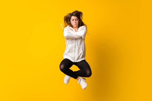 Giovane donna triste che salta sopra la parete gialla isolata
