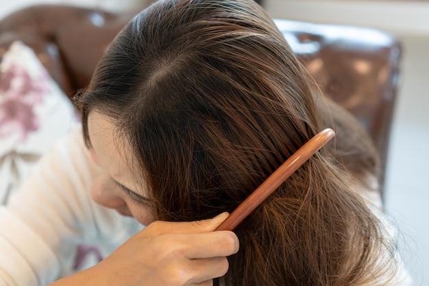 Giovane donna triste che spazzola i suoi capelli aggrovigliati.