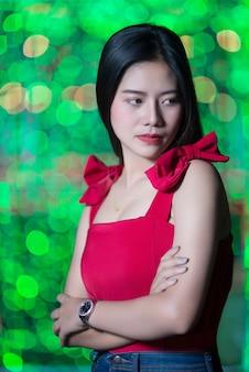 Giovane donna triste con luci della città astratta del bokeh