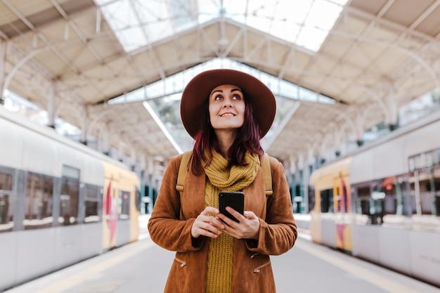 Giovane donna turistica alla stazione ferroviaria in attesa di prendere un treno e viaggiare. utilizzando il telefono cellulare e sorridente
