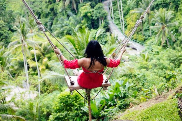 Giovane donna turistica che oscilla sopra la foresta pluviale tropicale all'isola di bali