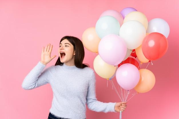 Giovane donna ucraina dell'adolescente che tiene i lotti dei palloni sopra la parete rosa isolata che grida con la bocca spalancata