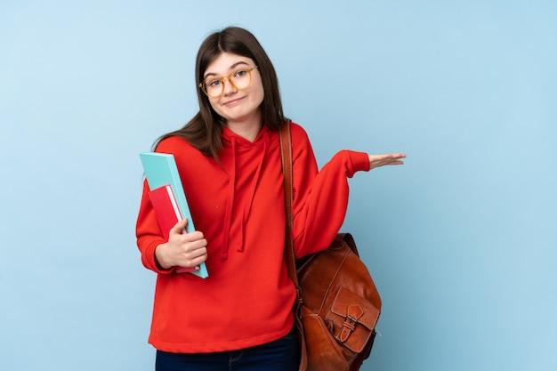 Giovane donna ucraina dello studente dell'adolescente che tiene un'insalata sopra la parete blu isolata che ha dubbi con l'espressione confusa del fronte