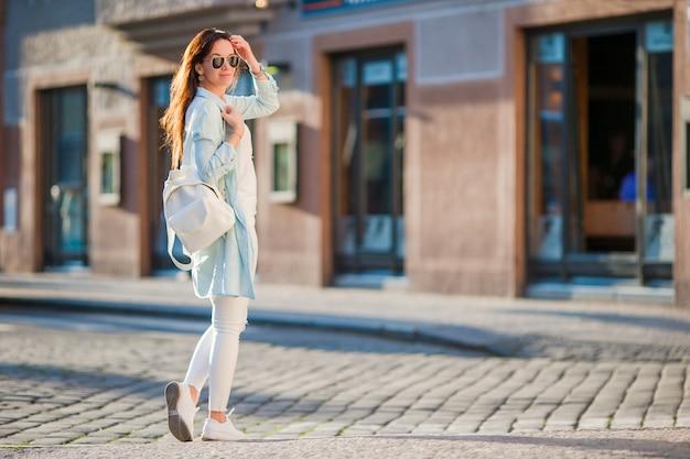 Giovane donna urbana felice in città europea sulle vecchie strade. turista caucasico che cammina lungo le strade deserte d'europa.