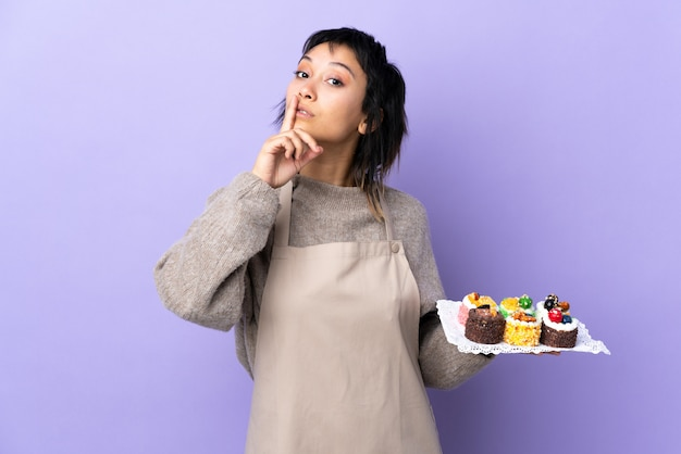 Giovane donna uruguaiana che tiene i lotti di mini mini torte differenti sopra la parete viola isolata che fa gesto di silenzio