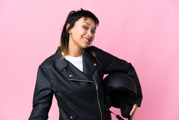 Giovane donna uruguaiana che tiene un casco del motociclo sull'applauso rosa isolato