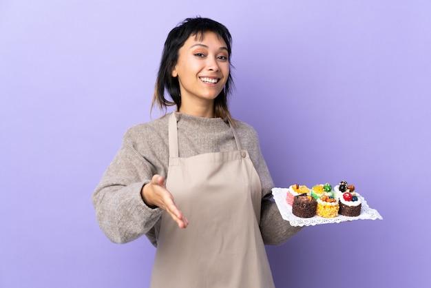 Giovane donna uruguaiana che tiene un sacco di diverse mini torte sopra la stretta di mano di muro viola dopo buon affare