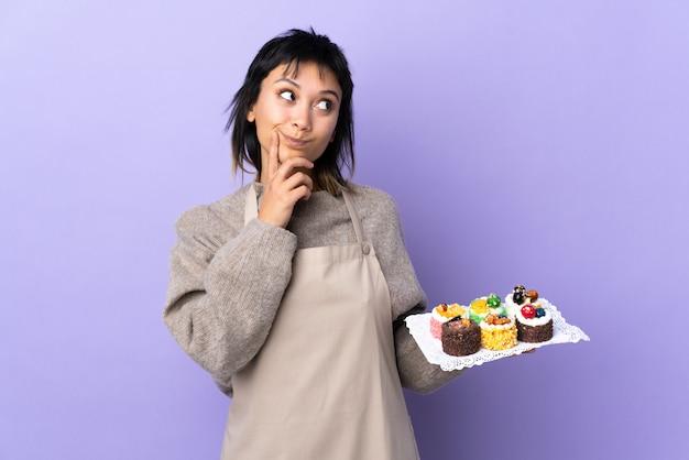 Giovane donna uruguaiana che tiene un sacco di mini torte diverse sul muro viola pensando un'idea