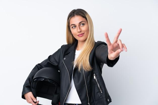 Giovane donna uruguaiana con un casco del motociclo sopra la parete bianca isolata che sorride e che mostra il segno di vittoria